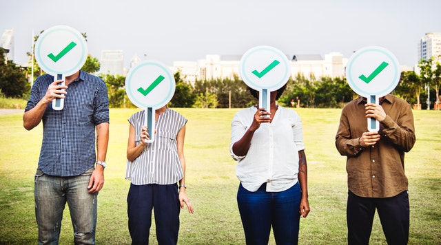 four people holding signs with a green checkmark over their face